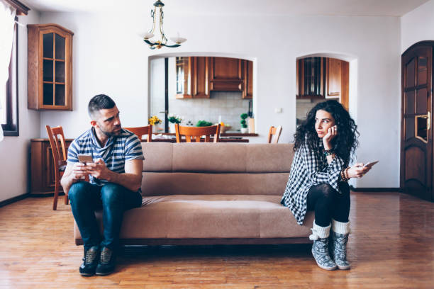 couple with relationship difficulties sitting on sofa at home - divorzio foto e immagini stock