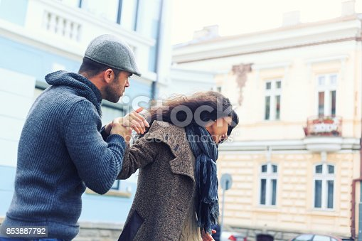 Young couple having relationship problems, breaking on street. Both with warm clothes.