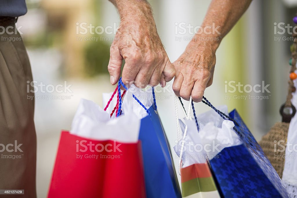 Couple With Shopping Bags Holding Little Fingers stock photo