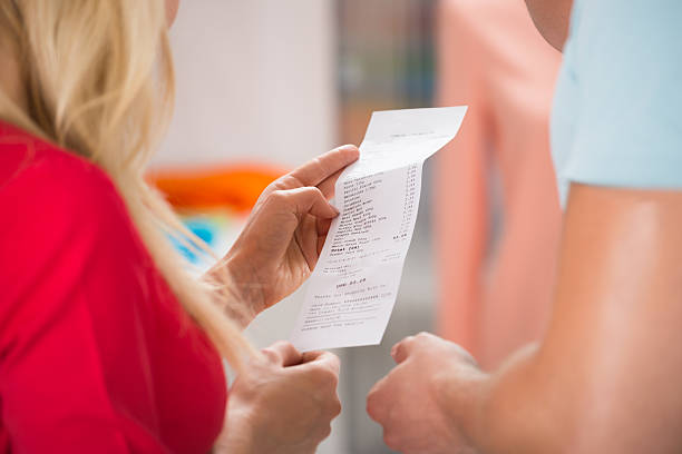 couple with shopping receipt in store - receipt stock photos and pictures
