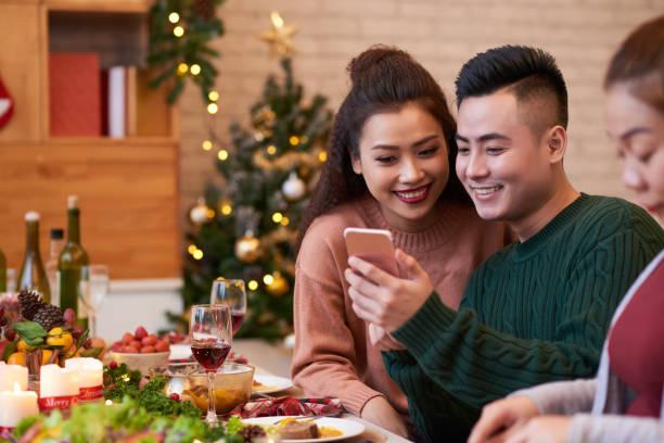 paar mit smartphone am esstisch - weihnachten vietnam stock-fotos und bilder
