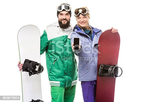 istock couple with snowboards showing smartphone 903670524