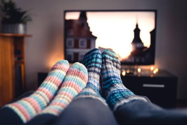 paar mit socken und wollene strümpfe gerade filme oder serien im fernsehen im winter. frau und mann sitzen oder liegen zusammen auf sofacouch im wohnzimmer mit online-streaming-dienst. - behaglich stock-fotos und bilder