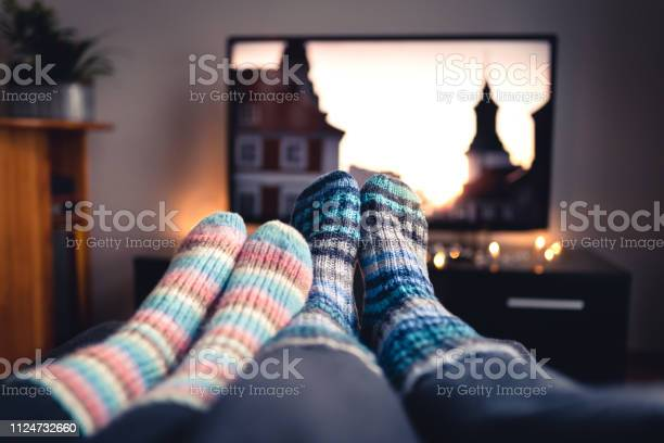 Photo of Couple with socks and woolen stockings watching movies or series on tv in winter. Woman and man sitting or lying together on sofa couch in home living room using online streaming service.