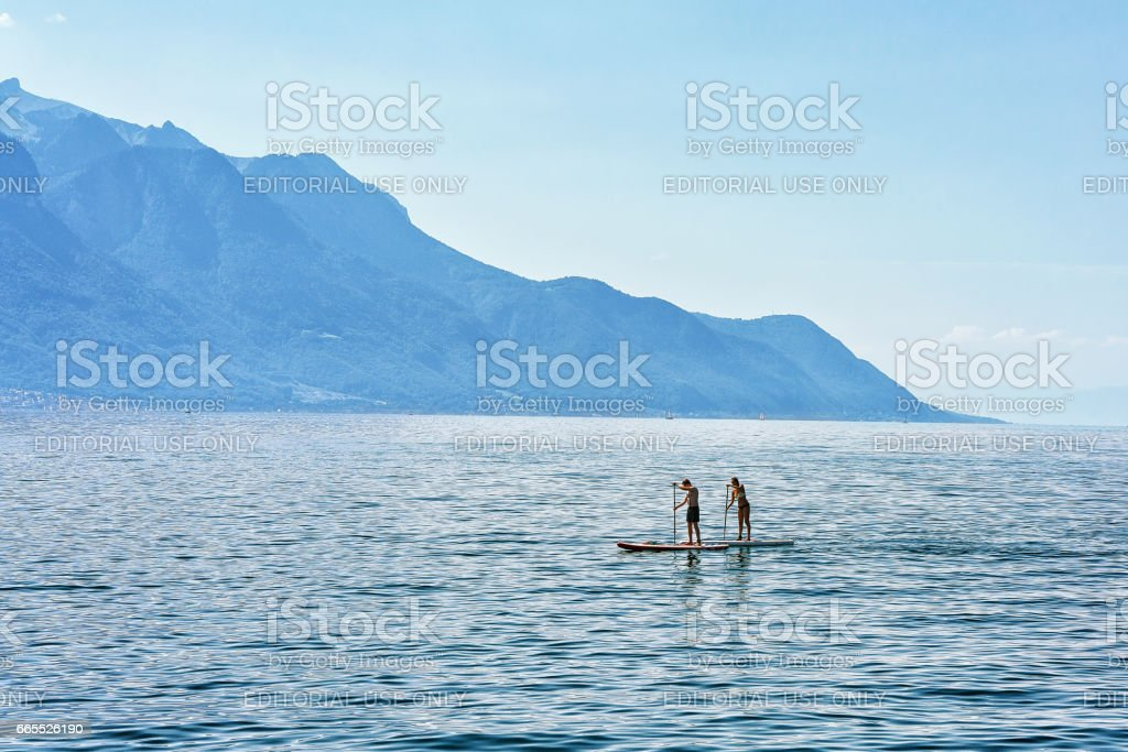 Couple with Standup paddle surfing board on Geneva Lake Montreux stock photo