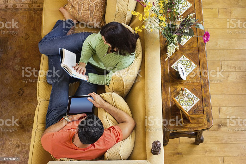 Couple With Tablet And Book On Sofa At Home royalty-free stock photo