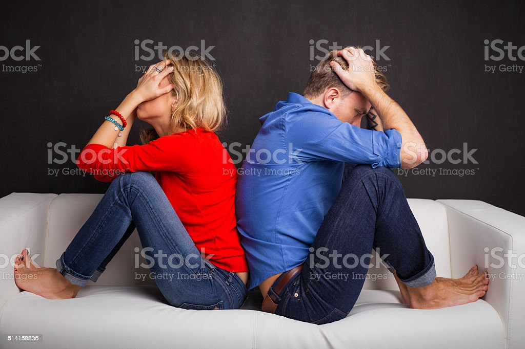 Couple with their backs turned to each other Couple with their backs turned to each other sitting on couch Adult Stock Photo