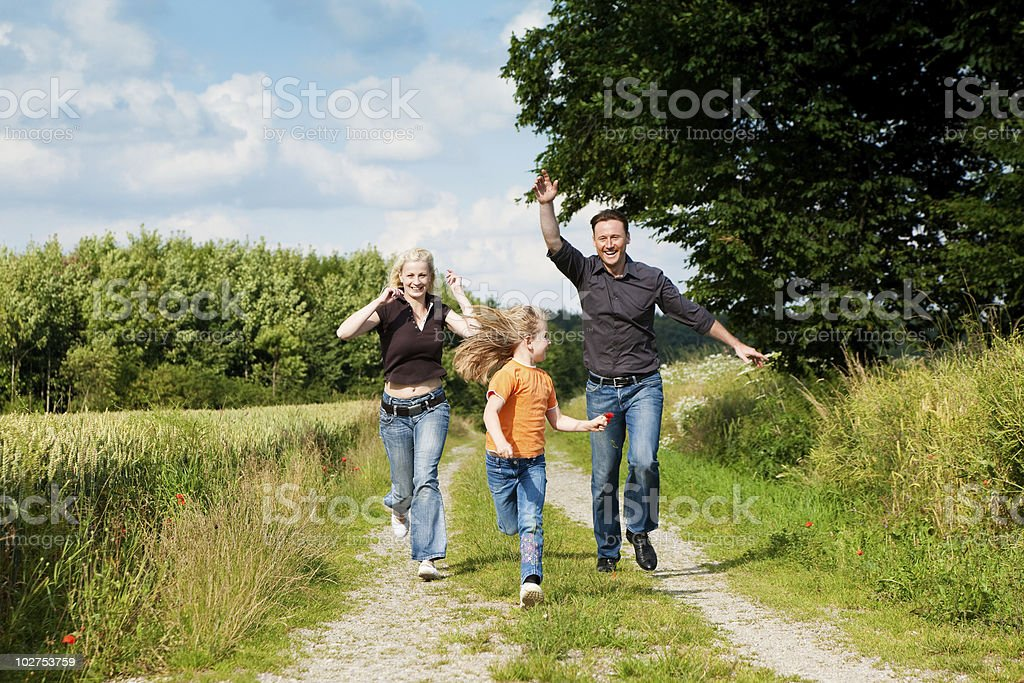 A couple with their child on a walk in the countryside royalty-free stock photo