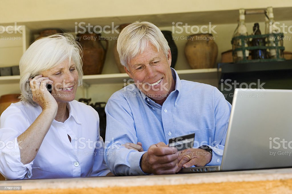 Couple with their mobile phone and laptop looking at a credit card royalty-free stock photo