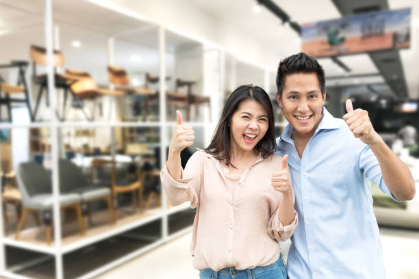 couple with thumb up in furniture showroom store Happy Asian couple with thumb up in furniture showroom store shopping couple asian stock pictures, royalty-free photos & images