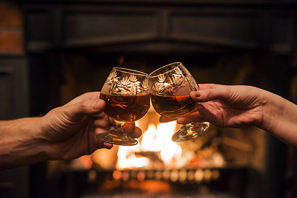 Couple with Two glasses of alcoholic drink  in front fireplace Couple with Two glasses of alcoholic drink  in front warm fireplace brandy stock pictures, royalty-free photos & images