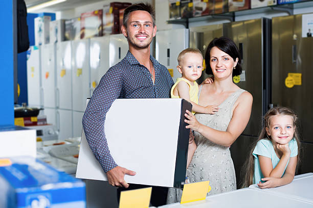 couple with two kids holding box with electronics - happy person buy appliances stock photos and pictures