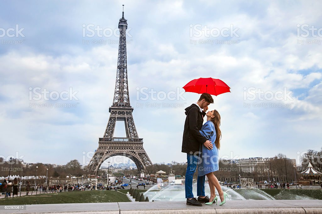 couple with umbrella near Eiffel Tower, honeymoon in Paris stock photo