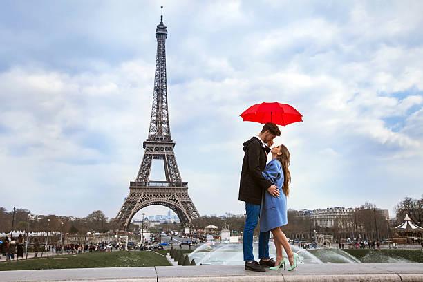 couple with umbrella near eiffel tower, honeymoon in paris - ikonische frauen stock-fotos und bilder