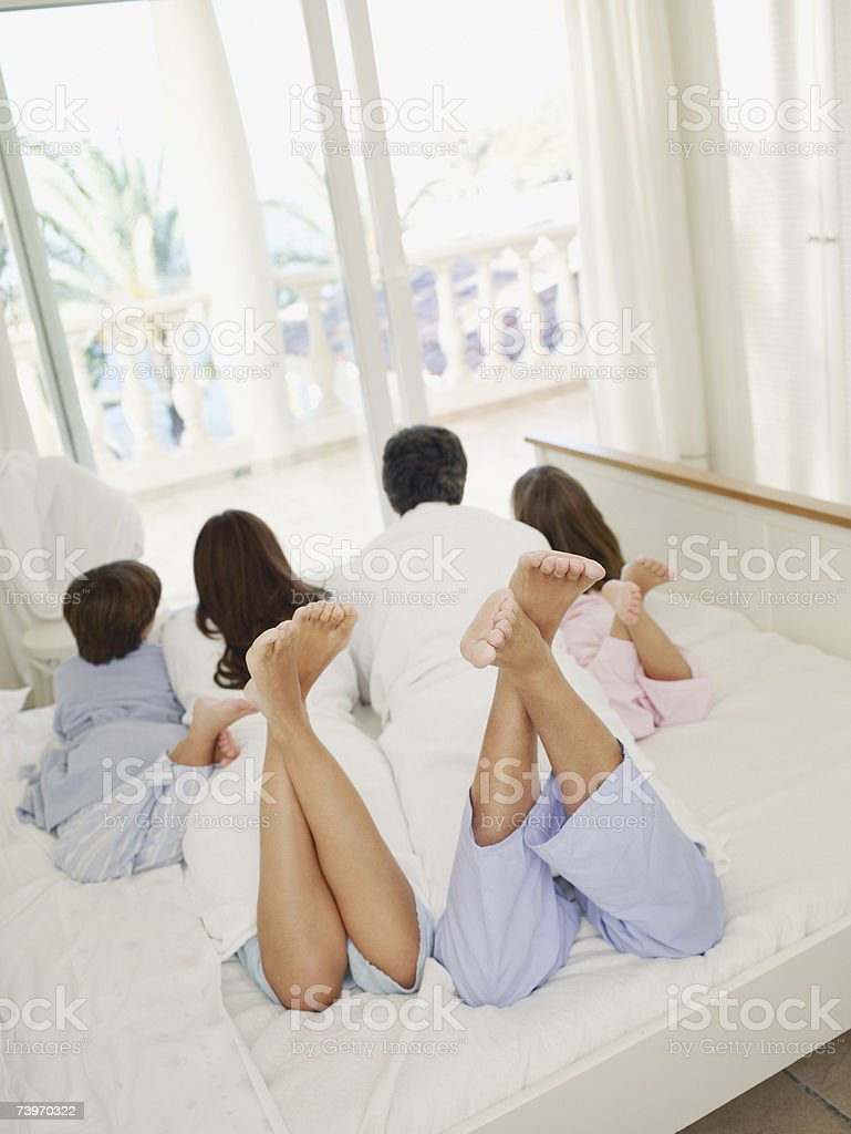 Couple with young daughter and son on bed lying on their stomachs royalty-free stock photo