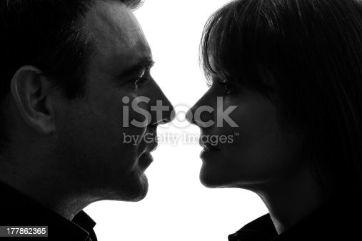 one caucasian couple woman man face to face in silhouette studio   on white background
