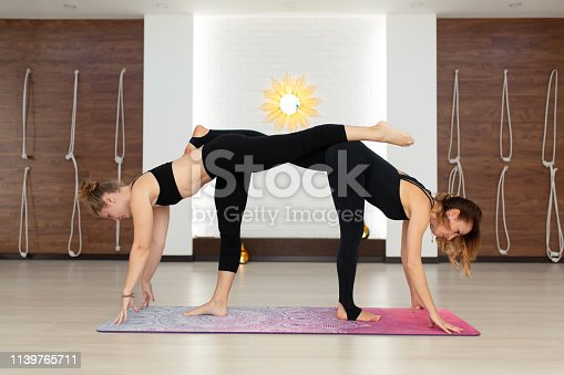 916126642istockphoto Couple womans in gym do yoga stretching exercises. Fit and wellness lifestyle 1139765711