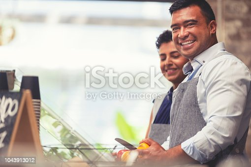 Couple working at a small retail food restaurant. They look like they are the small business owners. Both are ethnic and are working at the counter, happy and smiling.