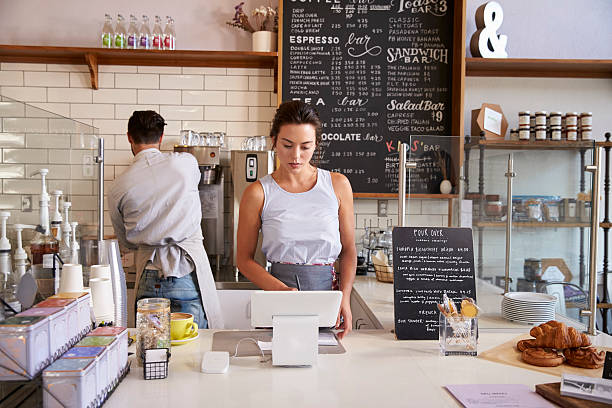 Couple working behind the counter at a coffee shop stock photo