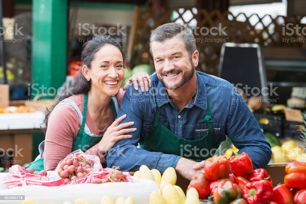 Couple working in fruit and vegetable stand stock photo