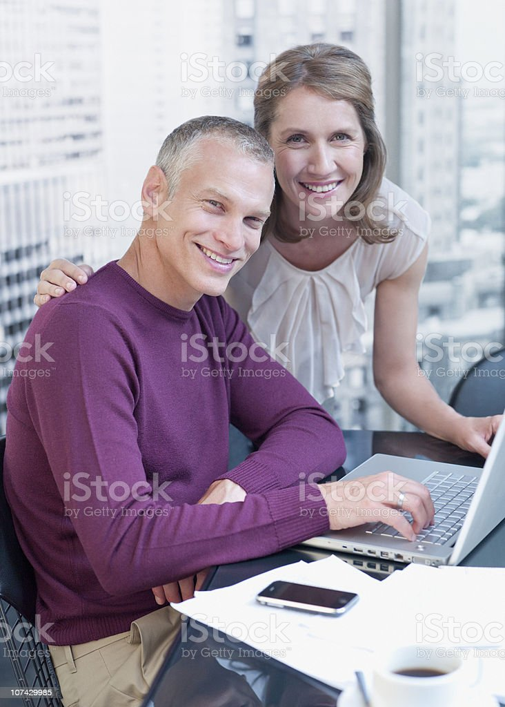 Couple working on computer with cityscape in background royalty-free stock photo