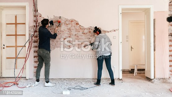 Young couple working on reconstruction of their apartment
