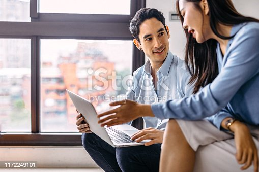 Young couple sitting and using laptops, together working on project at home.