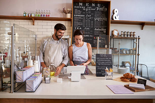 Couple working together at the till in a coffee shop stock photo