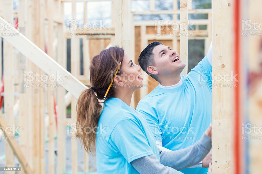 Couple working together to build home for charity stock photo