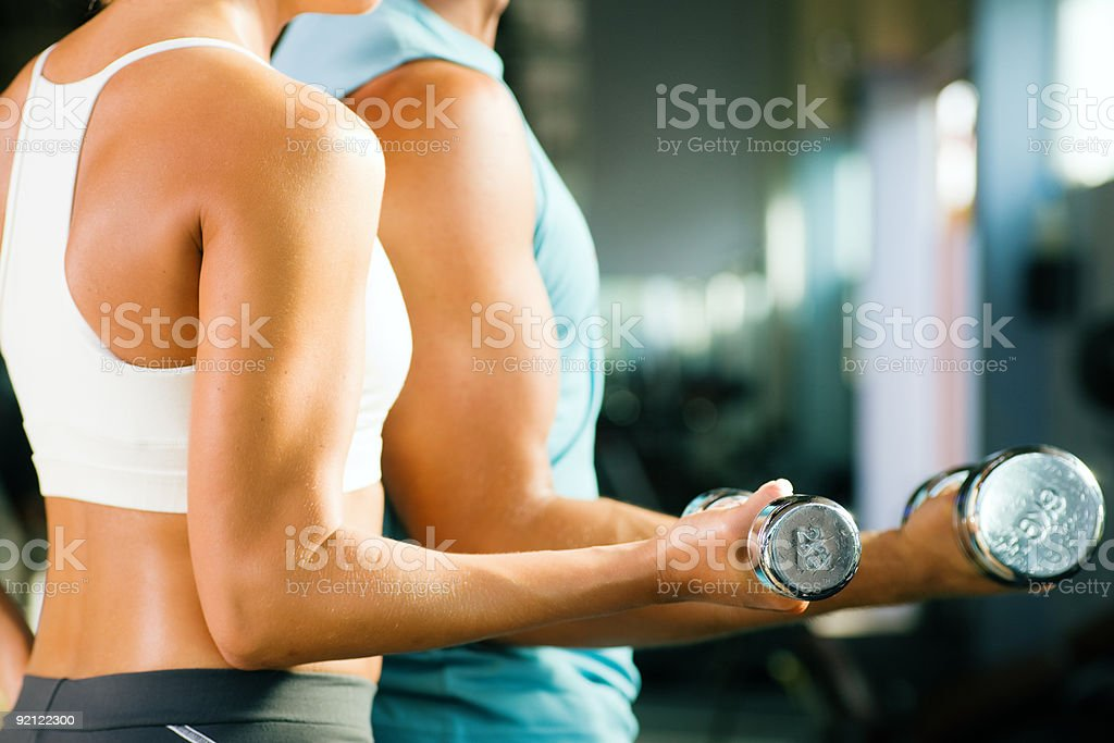 Couple works out together with dumbbells in a gym  Adult Stock Photo