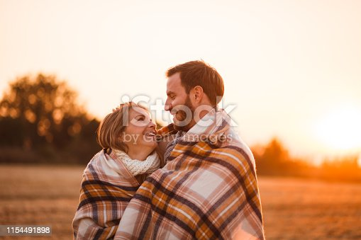Happy man and woman are standing in field during sunset, wrapped in a blanket.