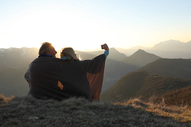 Couple wrapped in blanket take photo Swiss alps behind 55 59 years stock pictures, royalty-free photos & images