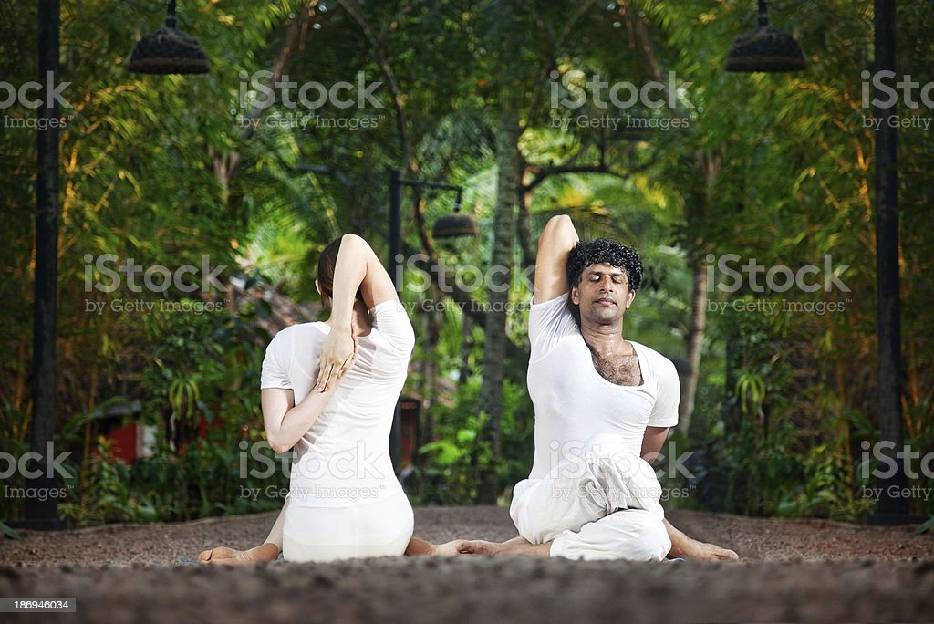 Couple yoga gomukhasana cow pose Couple Yoga of man and woman doing gomukhasana cow face pose front and back sides in white cloth in the garden Active Lifestyle Stock Photo