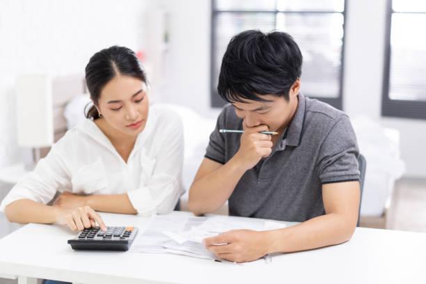 koppels berekenen uitgaven en rekeningen. het zijn stress - snavel stockfoto's en -beelden