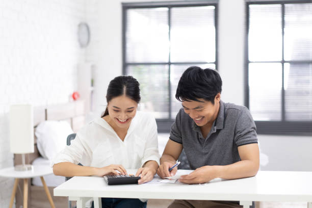 Couples are calculating expenses and bills.they are happy stock photo