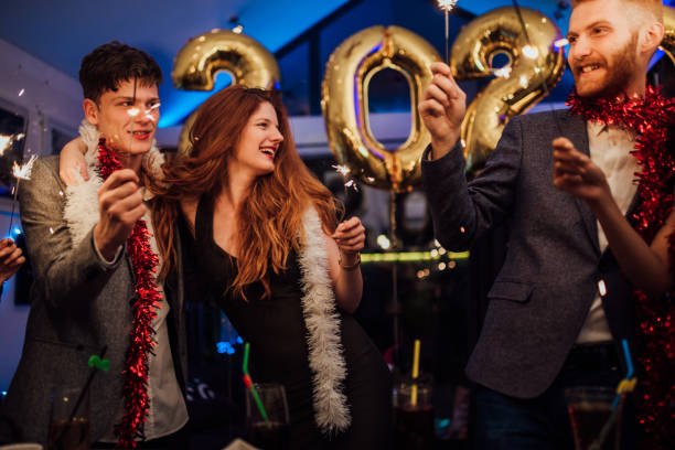 Couples celebrating New Year's Eve Two young couples celebrating New Years with sparklers 2020 2029 stock pictures, royalty-free photos & images