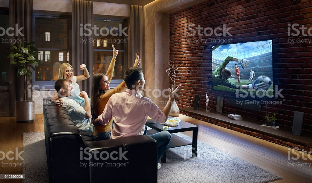 Couples cheering and watching soccer game on TV stock photo