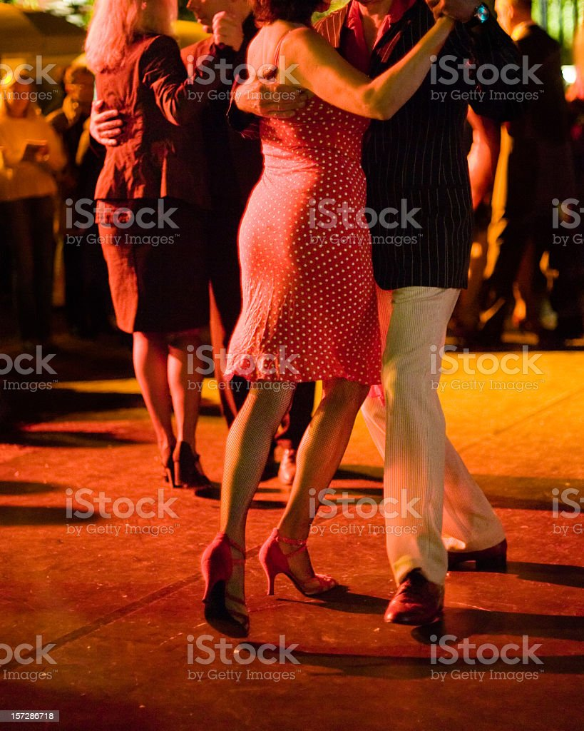 Couples dancing Argentine Tango outdoors at night, focus on legs. stock photo
