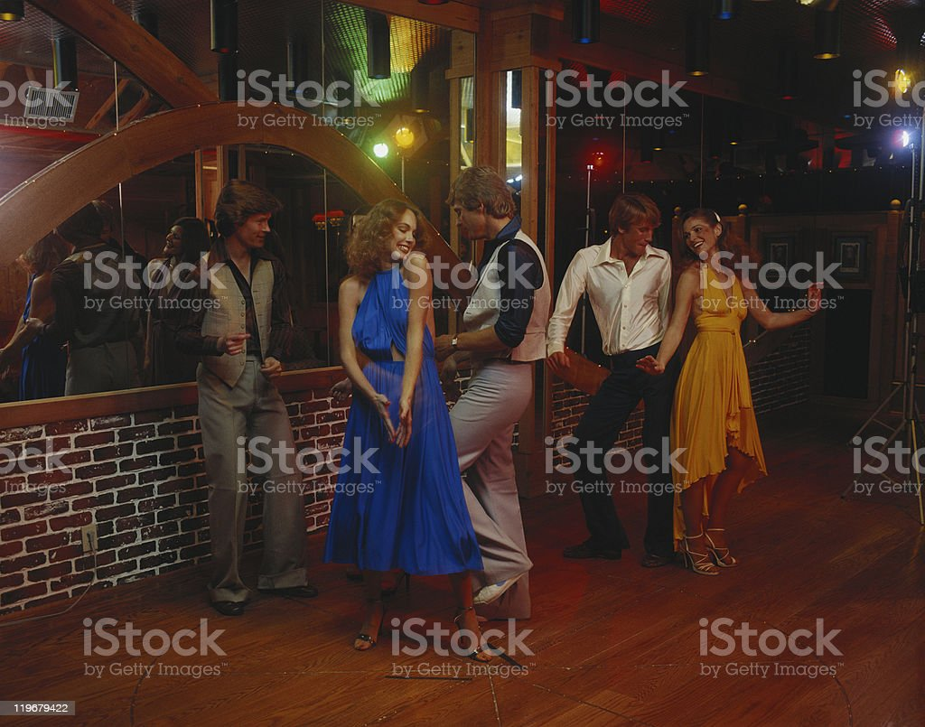Couples dancing together at nightclub, smiling stock photo