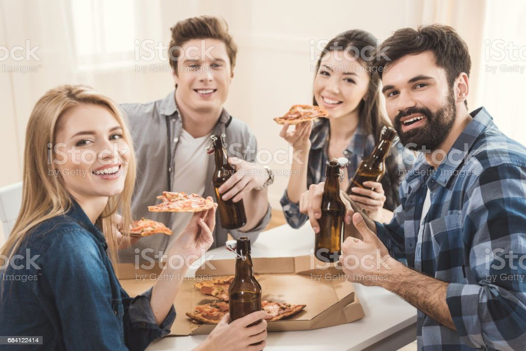 couples drinking beer and eating pizza foto stock royalty-free