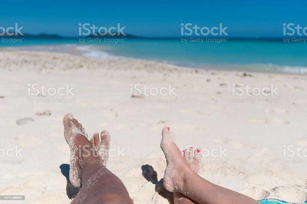 Couples feet in the sand on a deserted beach stock photo