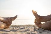 Couple's feet relax on white sand beach, sunrise in tropics