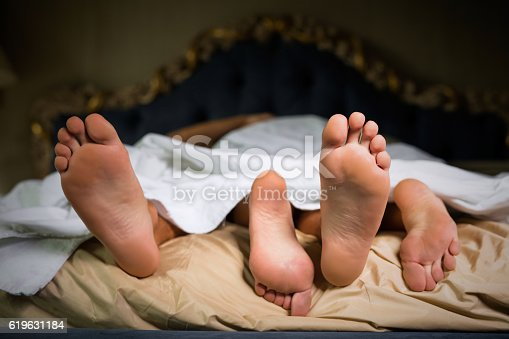 istock Couple's feet under sheets 619631184