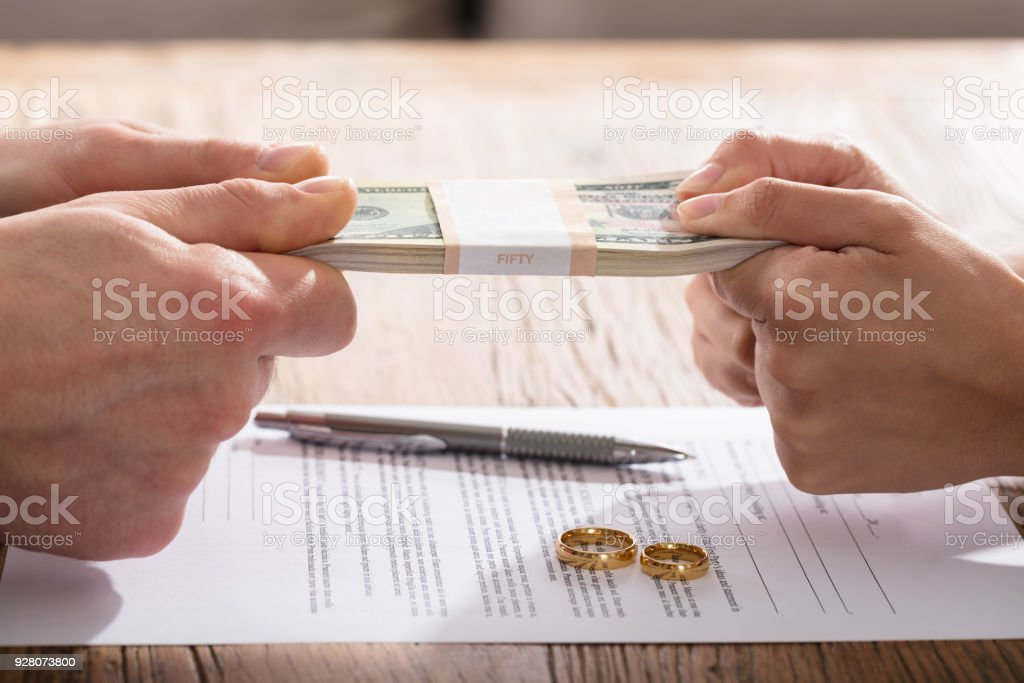 Couple's Hand Holding Currency Over The Divorce Agreement stock photo