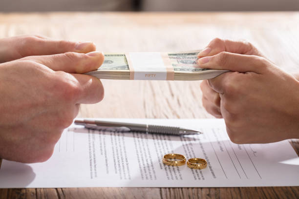 couple's hand holding currency over the divorce agreement - divorzio foto e immagini stock