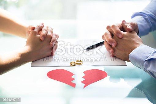 istock Couple's Hand On Divorce Paper 975124712