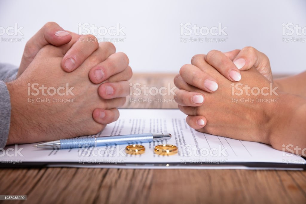Couple\'s Hand With Divorce Agreement And Golden Wedding Rings On...