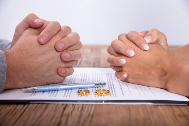 Couple's Hand With Divorce Agreement And Wedding Rings stock photo