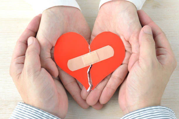 Couple's hands having broken heart with adhesive plaster stock photo