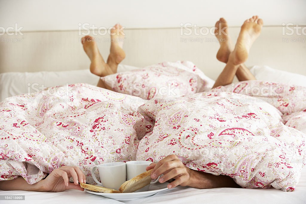 Couple's Hands Reaching From Under Duvet For Breakfast stock photo